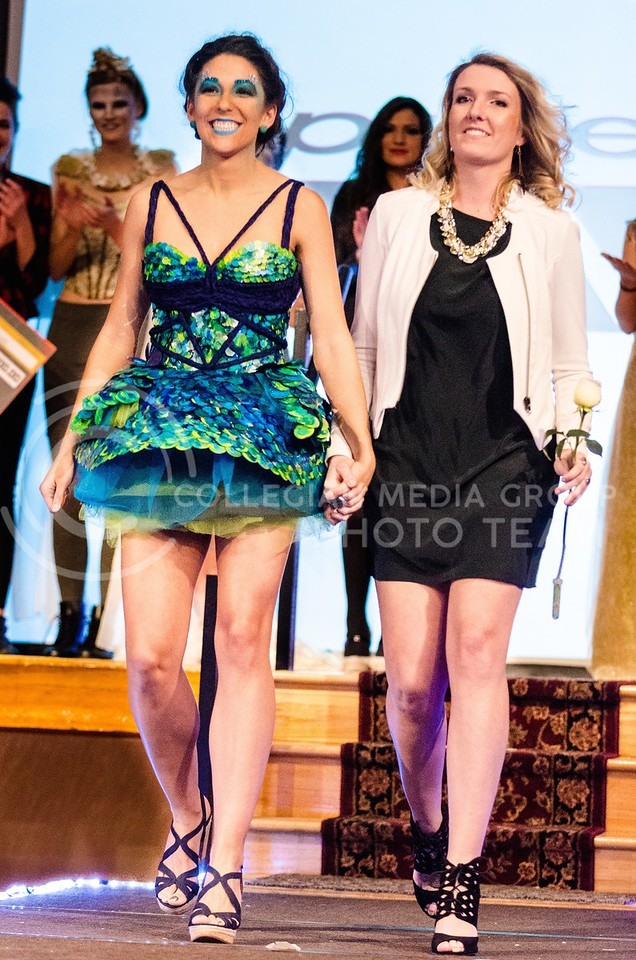 Photo by Parker Robb | The Collegian<br /> <br /> Arianna Levin, junior in apparel and textile design, walks down the runway with Sophia Alonso, senior in life sciences, modeling Levin's winning dress, to collect her prize for winning K-State Project Runway, Season 5: Hunger Games Challenge March 3, 2014. Faculty are not allowing Levin to enter her conservative lingerie designs in the Apparell & Design Showcase of Excellence, citing inappropriateness, although swimsuit designs are fair game.