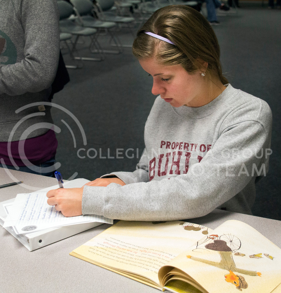 (Photo by Taylor Alderman | Collegian)<br /> <br /> Bridget Winter, sophomore in elementary education, writes notes for the picture book she is reading at the Mock Caldecott. The Mock Caldecott was held at the Manhattan Public Library on December 7, 2013.