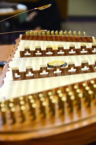 "Photo by Parker Robb | Collegian  Sarocha ""Mimi"" Pradyawong, PhD. student in biological and agricultural engineering, plays the khim, a Thai instrument very similar to a hammered dulcimer, for the enjoyment of attendees of the Thai Festival hosted by the Thai Student Association at the International Student Center February 15, 2014,. Enjoying good food with family while absorbing peaceful music is central to Thai culture."