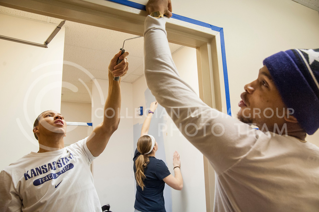 (Photo by Emily DeShazer   The Collegian)<br /> <br /> Volunteers Chris Campbell, a junior in military history, paints as Jharyl Bowry, a senior in social work, tapes the hallway at the Manhattan Arts Center Monday as part of Hands on K-State Martin Luther King Jr. day of service.  More than 300 participants helped in more than 20 locations around the community.