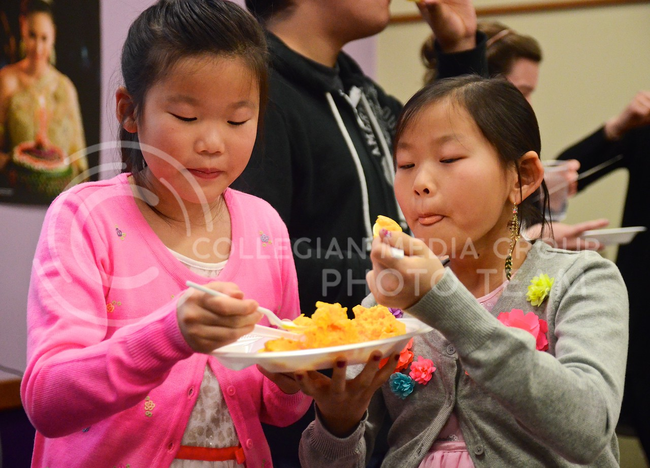 Photo by Parker Robb   Collegian<br /> <br /> Two young Thai Festival attendees enjoy Thai ice cream at the festival hosted by the Thai Student Association February 15, 2014, at the International Student Center.