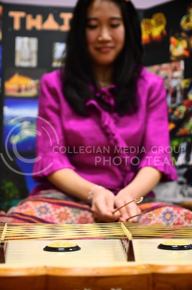 """Photo by Parker Robb   Collegian<br /> <br /> Sarocha """"Mimi"""" Pradyawong, PhD. student in biological and agricultural engineering, plays the khim, a Thai instrument very similar to a hammered dulcimer, for the enjoyment of attendees of the Thai Festival hosted by the Thai Student Association at the International Student Center February 15, 2014,. Enjoying good food with family while absorbing peaceful music is central to Thai culture."""