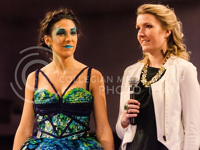 Photo by Parker Robb | The Collegian  Arianna Levin, junior in apparel and textile design, discusses the hand-painted sequins, imitating the scales of a fish and colors playing off the water, that she created for her dress, modeled by Sophia Alonso, senior in life sciences, at K-State Project Runway, Season 5: Hunger Games Challenge March 3, 2014. Levin, who finished runner-up last year, won the competition with her scaly dress inspired by the fishermen of District 4.
