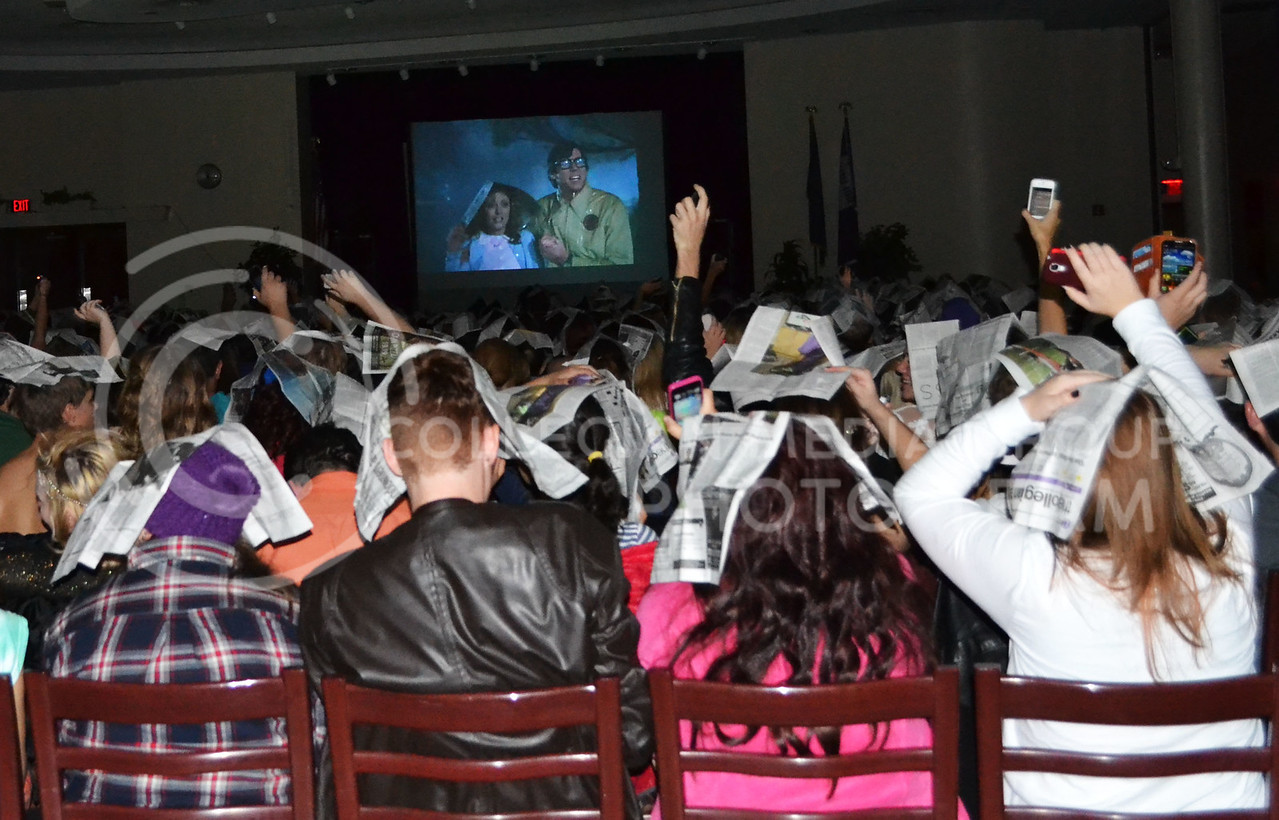 (Photo by Lauren Kuykendall | Collegian)<br /> <br /> During the Rocky Horror film the audience would use the provided props in their prop bags during certain scenes of the film. In this case everyone used a newspaper to cover their heads just as the actors in the film were to shield themselves from the rain.