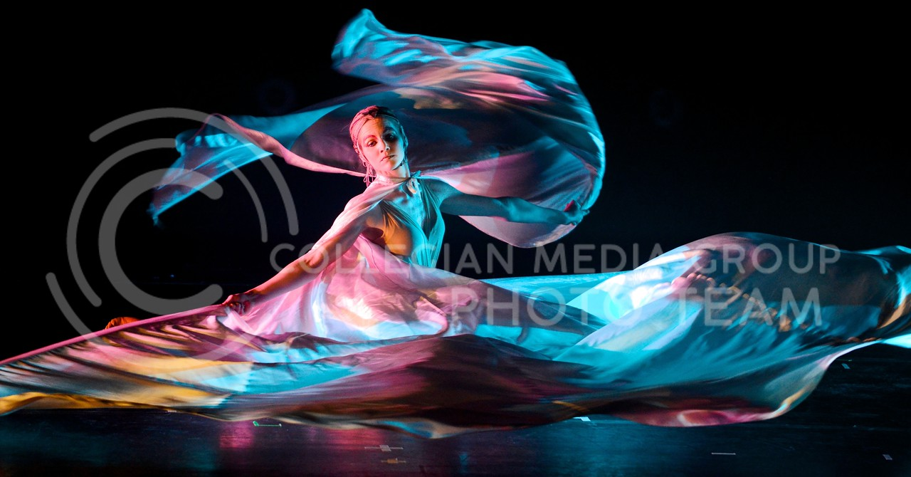 (Photo by Parker Robb   Collegian)<br /> <br /> A performer of the group Quixotic lets the differently-colored light flash and play off the sheets of her wings as she performs dance and acrobatics to beating music February 7, 2014, at McCain Auditorium.