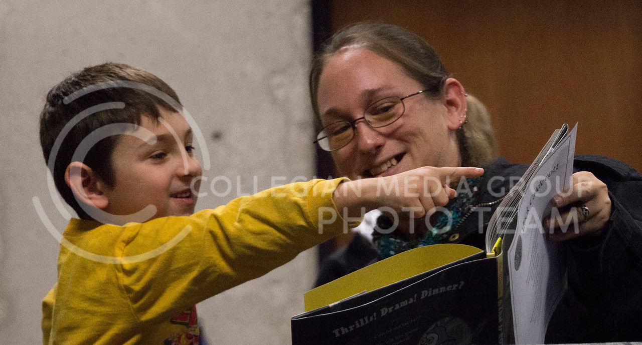 (Photo by Taylor Alderman   Collegian)<br /> <br /> Evven Morgenstern points at the picture book that he is reading with his mother, Erica Morgenstern at the Mock Caldecott on December 7, 2013 at the Manhattan Public Library. Erica is a member of K-State's Children's & Adolescent Literature Community (ChALC). The Mock Caldecott was sponsored by ChAlC, K-State Department of English and the Manhattan Public Library.
