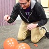 Photo by Parker Robb | The Collegian  Hoping to win one of three gift cards to local Manhattan businesses, Fred Amstutz, senior in public relations, wields a pushpin and attempts to pop as many balloons as he can before the other participants of Powercat Pop can February 27, 2014, in the Kedzie Library. Powercat PR, K-State's chapter of the Public Relations Student Society of America, hosted the event to promote Pop Money, a money transfer app, for the PRSSA Bateman competition.