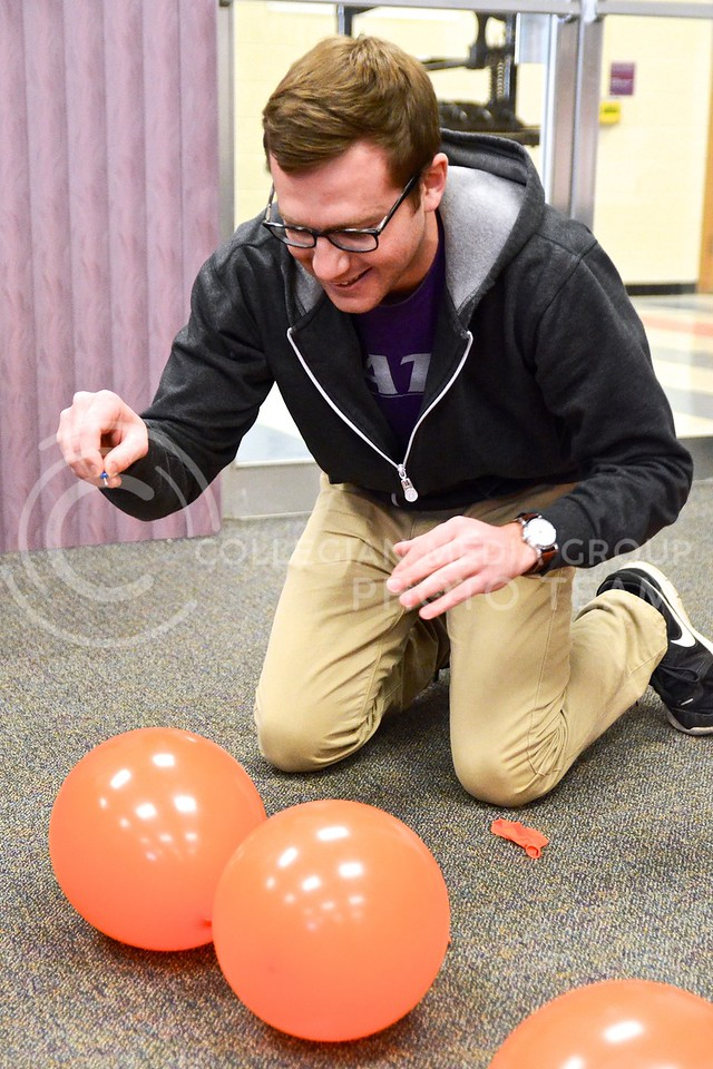 Photo by Parker Robb | The Collegian<br /> <br /> Hoping to win one of three gift cards to local Manhattan businesses, Fred Amstutz, senior in public relations, wields a pushpin and attempts to pop as many balloons as he can before the other participants of Powercat Pop can February 27, 2014, in the Kedzie Library. Powercat PR, K-State's chapter of the Public Relations Student Society of America, hosted the event to promote Pop Money, a money transfer app, for the PRSSA Bateman competition.