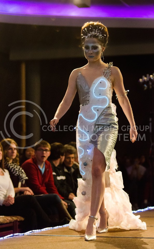 """Photo by Parker Robb   The Collegian<br /> <br /> Heidi Constant, senior in apparel and textile design, models the futuristic and high-tech-looking dress from District 3 designed by Victoria Uimscheid, junior in apparel and textile design, on the runway at K-State Project Runway, Season 5: Hunger Games Challenge March 3, 2014. District 3 was known for electronics in """"The Hunger Games"""" trilogy."""