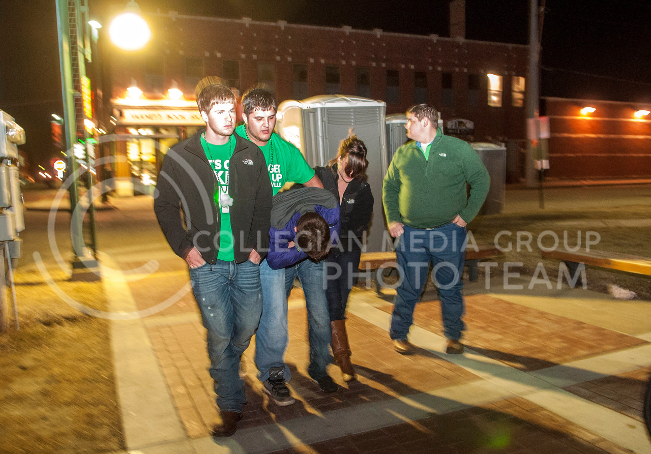 A group of friends help their friend stumble home after leaving Eighteen 63 on the evening Fake Patty's Day, Saturday, March 8.