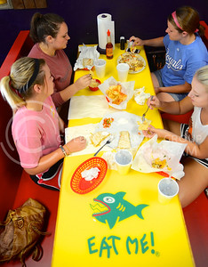 (Photo by Parker Robb | Collegian)  From left to right, Ashley Ladd, junior in life science and pre-vet, Mary Harness, junior in sociology, Claire Finkle, senior in advertising and Kati Krieg, junior in english, enjoy their meal underneath the fish adorning the wall of Fuzzy's Taco Shop Tuesday evening. The restaurant with the funny name recently opened in Aggieville in the property vacated by the Hibachi Hut.