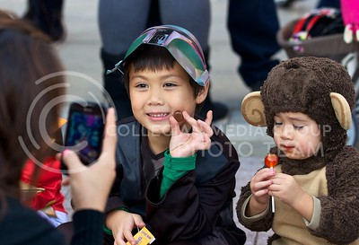 Photo by Jed Barker   The Collegian  Ody Naylor (left), dressed as a bounty hunter in Star Wars, smiles as his mother snaps a few photos of him and his brother, Agam, as they wait for the K-State homecoming parade to pass through Aggieville on October 25, 2013.