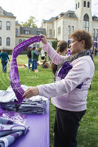 (Photo by Minh Mac   The Collegian)  Barbara Lippman, admistrative specialist of the office of international programs, looks at a banner at the merchandise table  Celebration of the 150th Grand Finale and closing ceremonies reception were held on the Anderson Hall lawn, on Thursday, Oct. 24, 2013. Comers were given free t-shirts, and the special 150 K-birthday flavored Call Hall ice-cream.