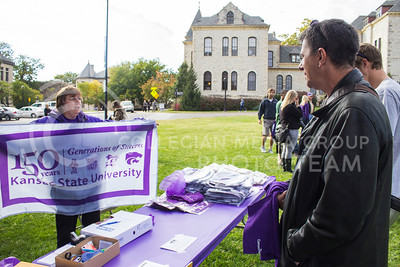 (Photo by Minh Mac   The Collegian)  Larie Schoap, a 78' alumnus, holds up the 150 years Kansas State University - Generations of Success flag at the the merchandise table.  Celebration of the 150th Grand Finale and closing ceremonies reception were held on the Anderson Hall lawn, on Thursday, Oct. 24, 2013. Comers were given free t-shirts, and the special 150 K-birthday flavored Call Hall ice-cream.