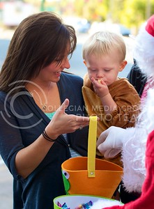 Photo by Jed Barker   The Collegian  Kylan Viar holds one year old Dawson Clark, who is dressed up in a monkey suit, as they fill up their basket with candy during Trick-or-Treat in Aggieville on October 25, 2013.