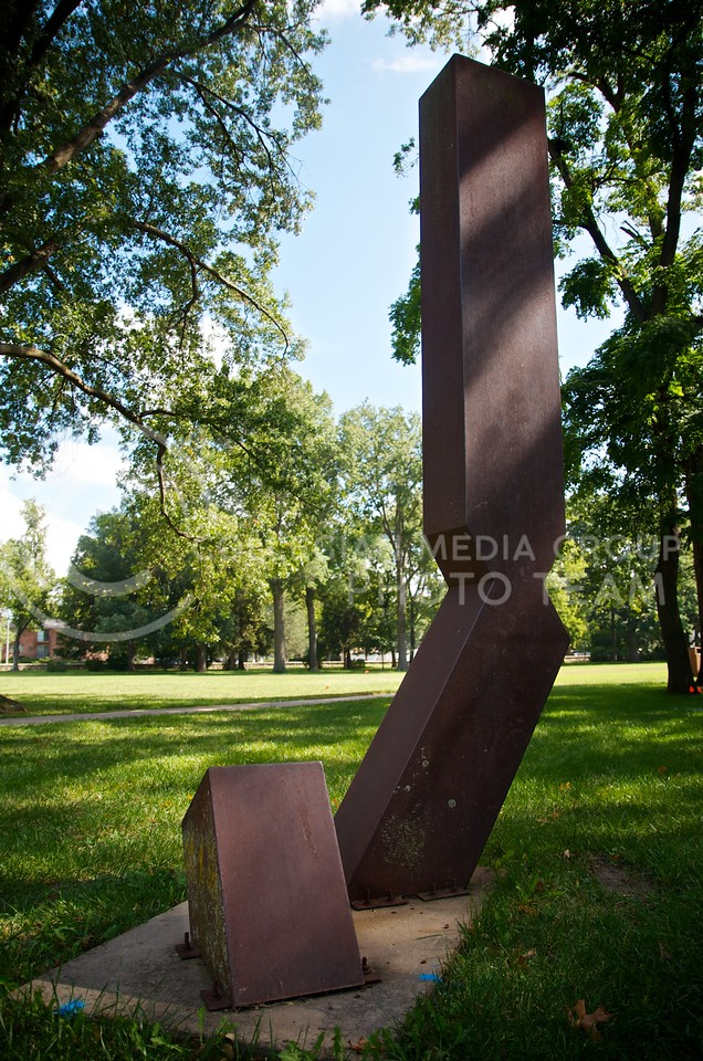 "(Photo by Parker Robb | Collegian)  <br /> <br /> This untitled piece, created by an unknown artist during the ""Art in Situation"" workshop, and located east of the President's Residence and south of Justin Hall, is composed of cor-ten steel welded together."