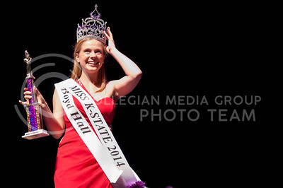 Abby Alsop, freshman in microbiology, and representative of Boyd Hall holds her crown to keep it from falling after accepting her title as Miss K-State 2014 in McCain Auditorium Tuesday night.  Twenty contestants from organization all over campus participated in second year of the Miss K-State competition. Twenty contestants from various K-State organizations competed in the 2014 Miss K-State competition on Tuesday, April 15, in McCain Auditorium. Abby Alsop, freshman in microbiology, representing Boyd Hall won the title, taking it over from Kaitlyn Dewell, of Gamma Phi Beta.