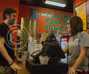 (Photo by Taylor Alderman | Collegian)  Tom Blevins, junior in clinical laboratory science, looks at the menu as Kristen Doll, general manager of Fuzzy's Taco Shop takes his order.