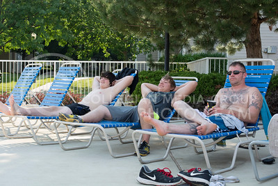Photo by George Walker | The Collegian  Sophomore Breenan Neumayer, Freshman Chase Pfieffer, and Marten Dresen tan near the pool at University Crossing on Monday July 21, 2014. Many people who live at the apartment complex invite friends to the pool with them.