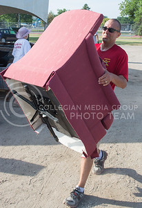 Photo by George Walker | The Collegian   unloads a chair that was donated to the Furniture Amnesty Day event in City Park on July 25, 2014. Many volunteers and donors work together to make the Furniture Amnesty Day happen.