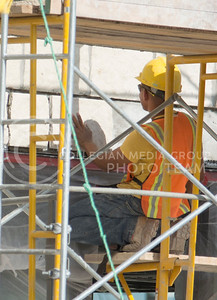 Photo by George Walker | The Collegian  A construction worker attaches a stone panel to the Bluemont Hotel on June 30, 2014. The Bluemont Hotel is set to open September 17th, 2014.