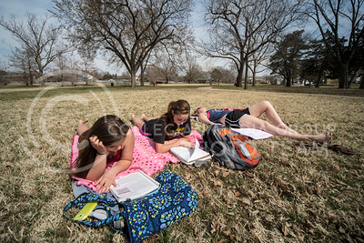 A trio of K-State students study and sunbathe in City Park on March 30. CIty Park also offers a playground, a public pool, tennis courts and baseball fields.