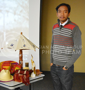 (Photo by George Walker | Collegian) Nathanaël Razafindrabe, a sophomore at Barton Community College in Great Bend, Kansas, stands next to some hand-crafted items from his native country, Madagascar. Razafindrabe is a cousin of Manase, the presenter at the Coffee Hour.