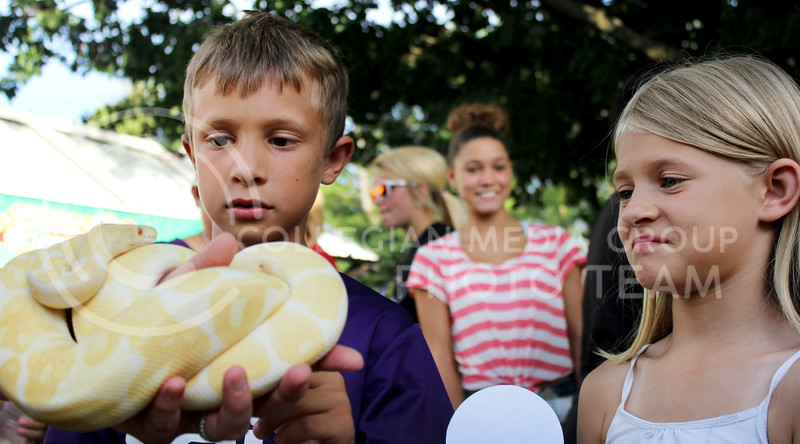 Chandler Rilley   Collegian  Aaron, 10, and Emily, 8, gaze at a yellow ball python at a booth during Purple Power Play in the Park Wednesday night in City Park.