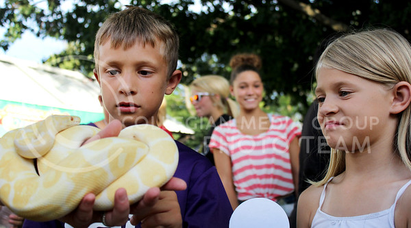 Chandler Rilley | Collegian  Aaron, 10, and Emily, 8, gaze at a yellow ball python at a booth during Purple Power Play in the Park Wednesday night in City Park.