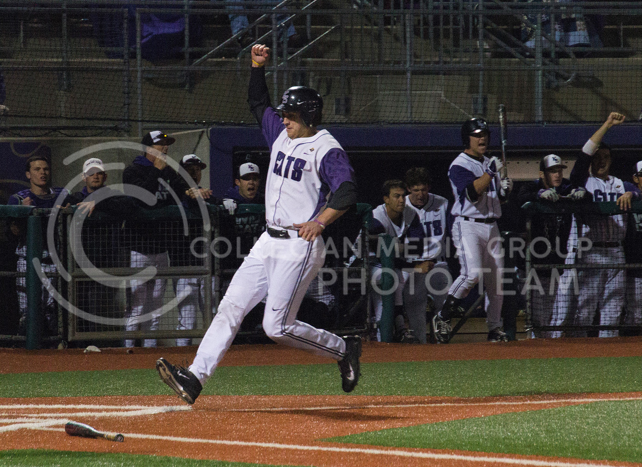 (Photo by Taylor Alderman | Collegian)<br /> <br /> Ross Kivett, senior infielder, raises a fist as he runs into home scoring a run as his team cheers in the dugout. K-State defeated Baylor 8-2 in the first game of the series on April 17, 2014 at Tointon Family Stadium.