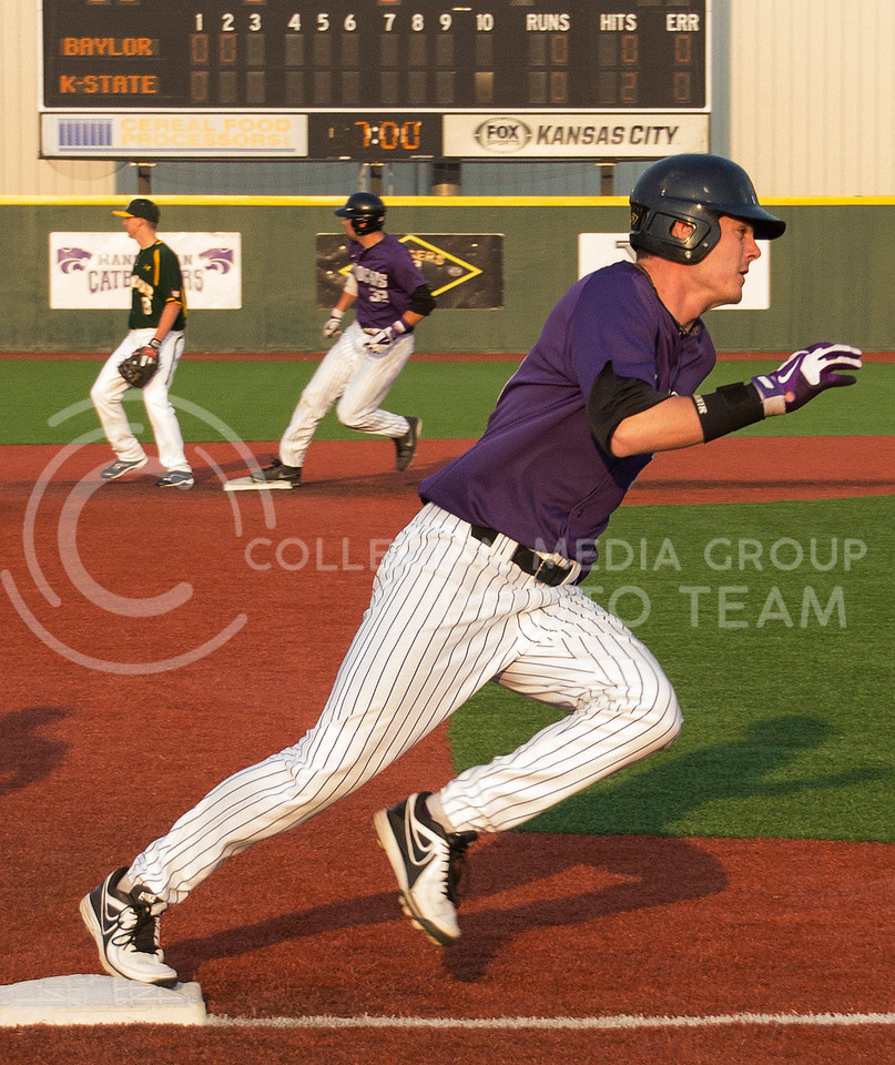 (Photo by Taylor Alderman | Collegian)<br /> <br /> Shane Conlon, junior infielder, rounds third base towards home plate as Tyler Stover, freshman infielder, steps onto second base. K-State beat Baylor 6-2 on April 18, 2014 at Tointon Family Stadium.