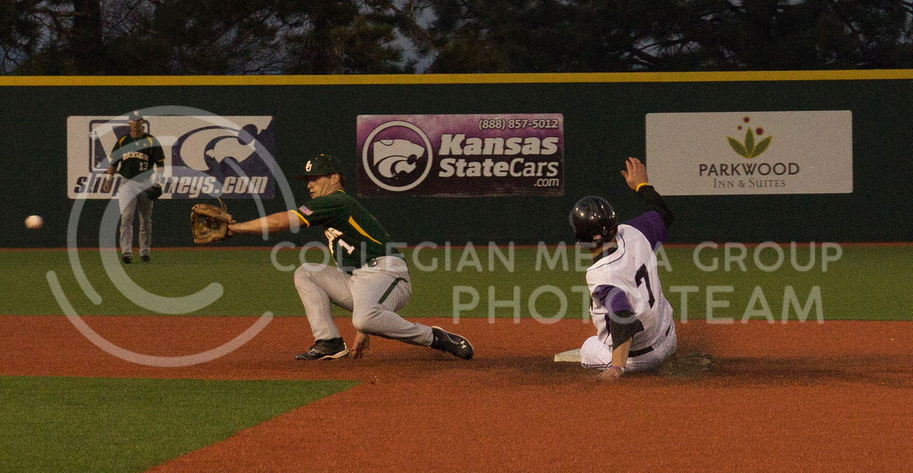 (Photo by Taylor Alderman | Collegian)<br /> <br /> Ross Kivett, senior infielder, slides into second base as Baylor's Brett Doe attempts to get him out on April 17, 2014 at Tointon Family Stadium. The Cats defeated the Bears 8-2 during the first game in the series.