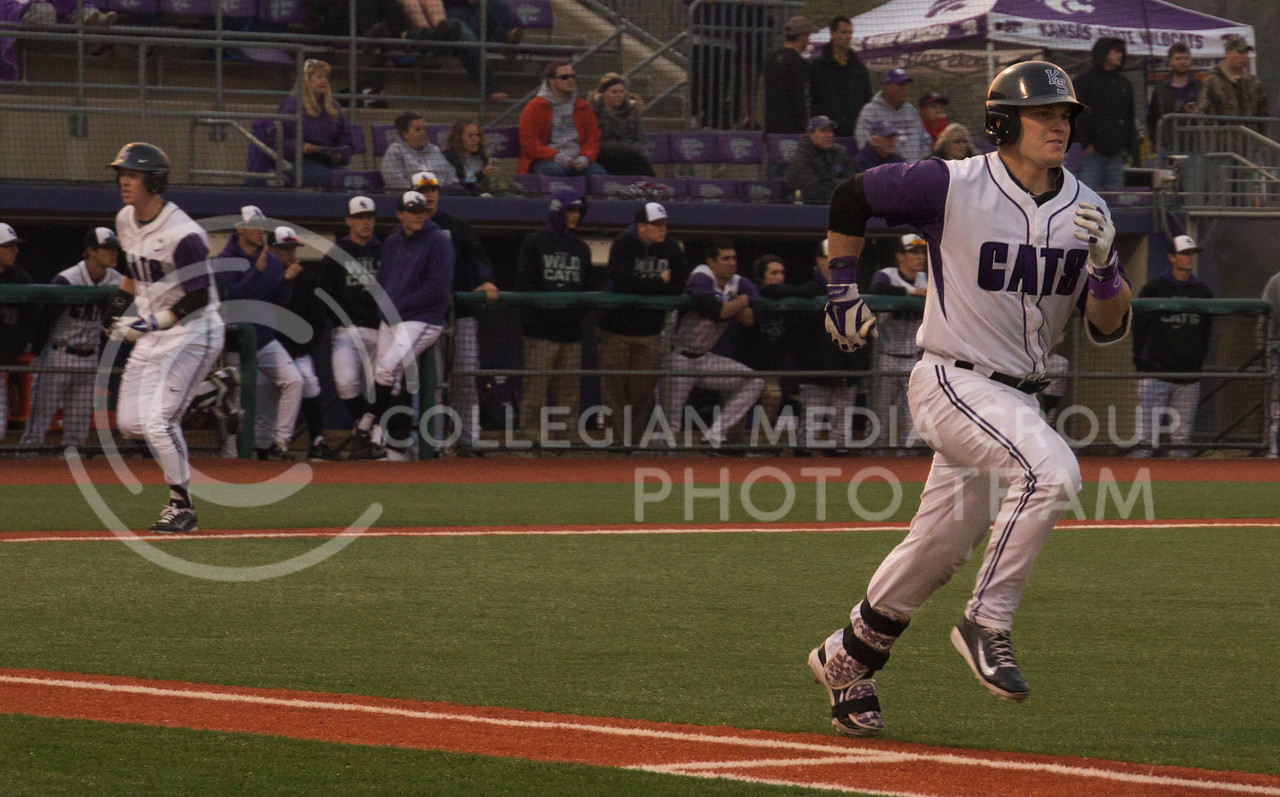 (Photo by Taylor Alderman | Collegian)<br /> <br /> Blair DeBord, senior catcher, runs the baseline as Max Brown, junior outfielder, sprints to score a run. The Cats beat Baylor 8-2 on April 17, 2014 at Tointon Family Stadium.