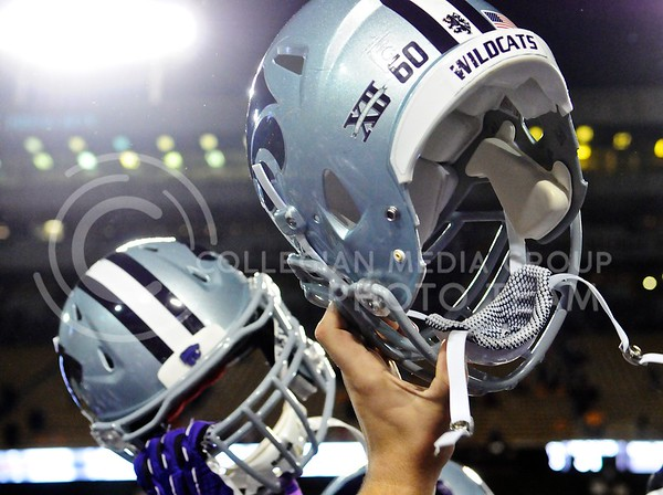 (Photo by Parker Robb | Collegian)  K-State players raise their helmets in celebration after defeating Michigan 31-14 in the Buffalo Wild Wings Bowl December 28, 2013, bringing K-State its first bowl victory since 2002.