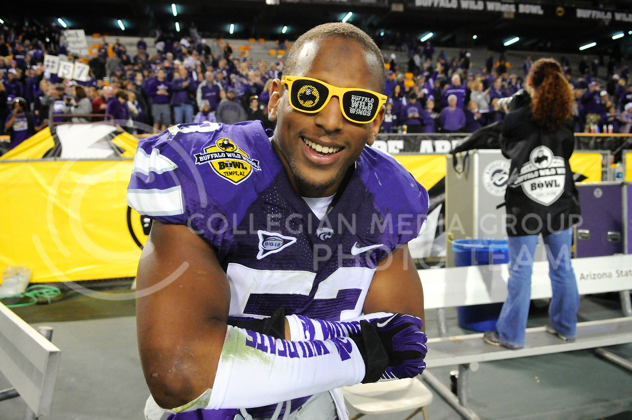 (Photo by Parker Robb   Collegian)<br /> <br /> Senior defensive back Blake Slaughter celebrates the Wildcats' victory by wearing a pair of Buffalo Wild Wings Bowl sunglasses after defeating Michigan in the game December 28, 2013.