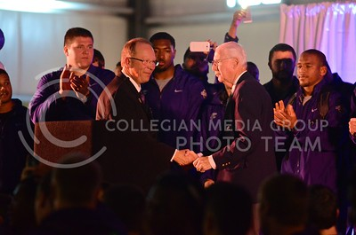 (Photo by Parker Robb | Collegian)  The voice of the Wildcats Wyatt Thompson, MC for the pep rally, shakes hands with head football coach Bill Snyder as he takes the stage at the K-State bowl game pep rally at Rawhide Western Town in Phoenix December 27, 2013.