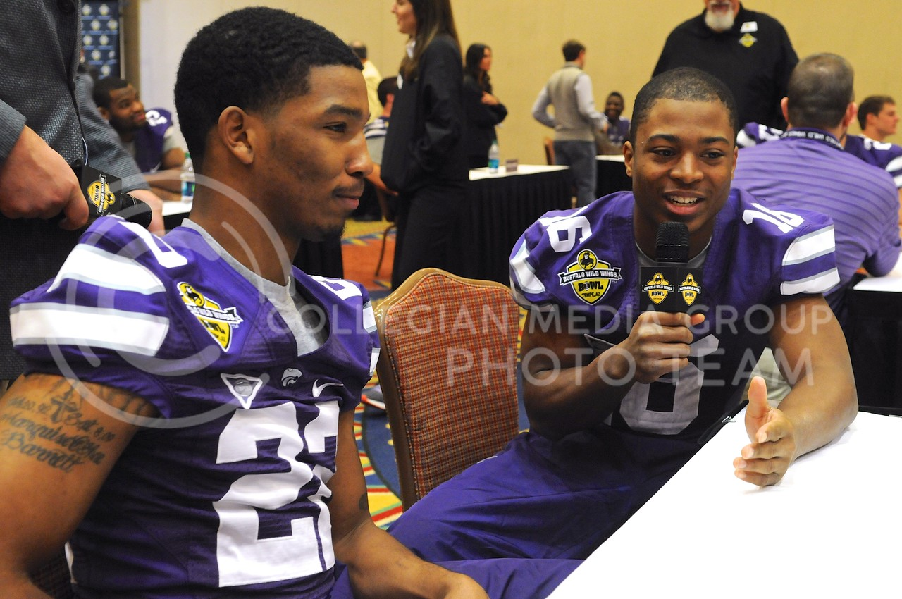 (Photo by Parker Robb | Collegian)<br /> <br /> Junior wide receiver Tyler Lockett, interviewee turned interviewer, questions sophomore defensive back Dante Barnett during K-State's Buffalo Wild Wings Bowl media day December 26, 2013.
