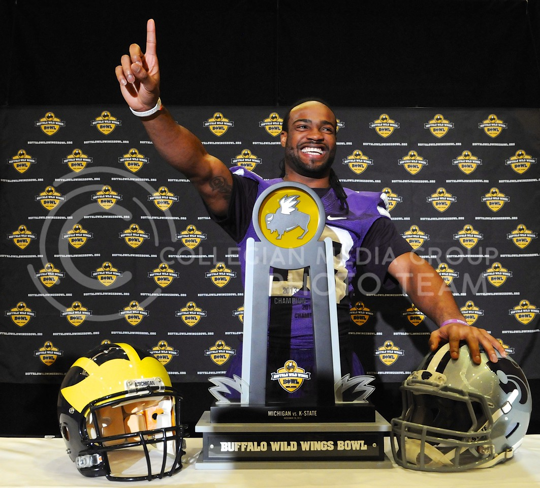 (Photo by Parker Robb | Collegian)<br /> <br /> Senior running back John Hubert is all smiles as he poses with the trophy and predicts who will win during K-State's Buffalo Wild Wings Bowl media day December 26, 2013.