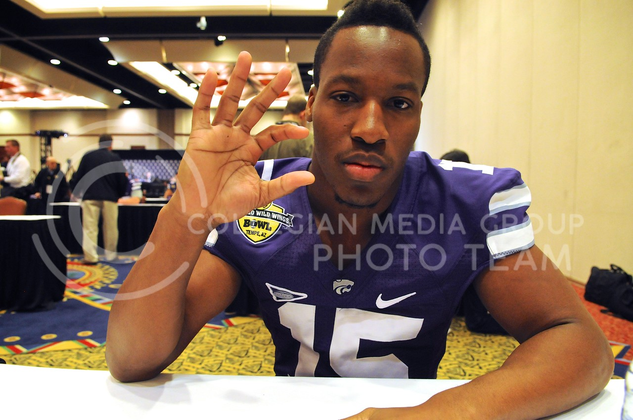 (Photo by Parker Robb | Collegian)<br /> <br /> Junior defensive back Randall Evans gives the wildcat sign during K-State's Buffalo Wild Wings Bowl media day December 26, 2013.