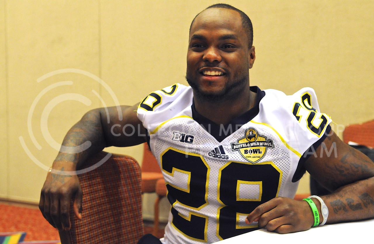 (Photo by Parker Robb | Collegian)<br /> <br /> Michigan running back Fitzgerald Toussaint responds to questions from the media during Michigan's Buffalo Wild Wings Bowl media day December 26, 2013.