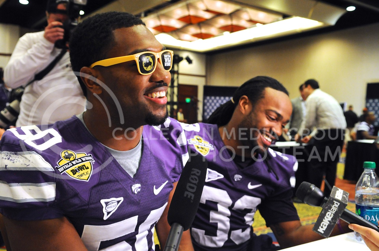 "(Photo by Parker Robb | Collegian)<br /> <br /> Senior linebacker Tre Walker and senior running back John Hubert laugh in embarrassment after singing their own rendition of ""My Girl"" in response to a question on secret talents among the wildcat roster during K-State's Buffalo Wild Wings Bowl media day December 26, 2013."