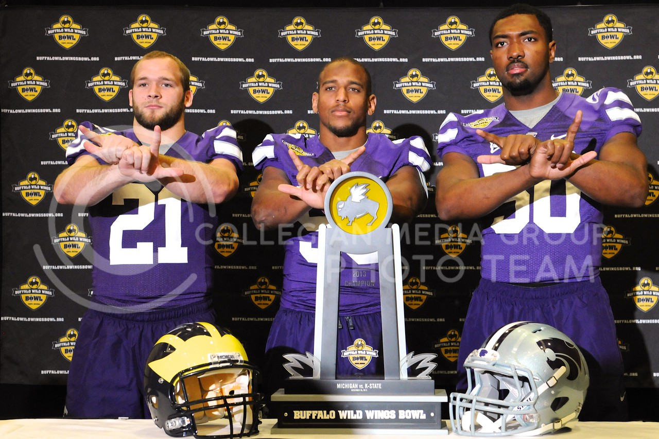 (Photo by Parker Robb | Collegian)<br /> <br /> From left to right, junior linebacker Jonathan Truman, senior line backer Blake Slaughter and senior linebacker Tre Walker pose behind the Buffalo Wild Wings Bowl champion's trophy during K-State's Buffalo Wild Wings Bowl media day December 26, 2013.