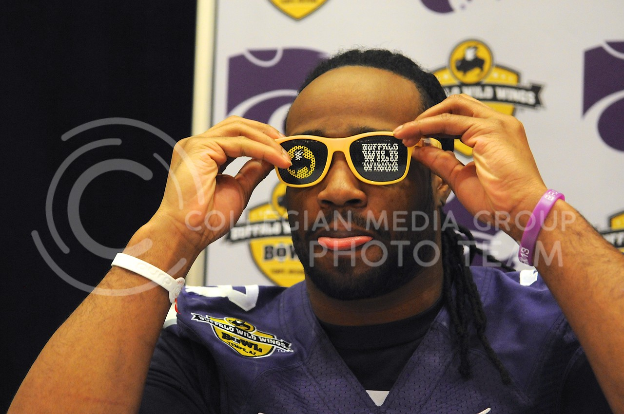 (Photo by Parker Robb | Collegian)<br /> <br /> Senior running back John Hubert puts on a pair of Buffalo Wild Wings specs during K-State's Buffalo Wild Wings Bowl media day December 26, 2013.