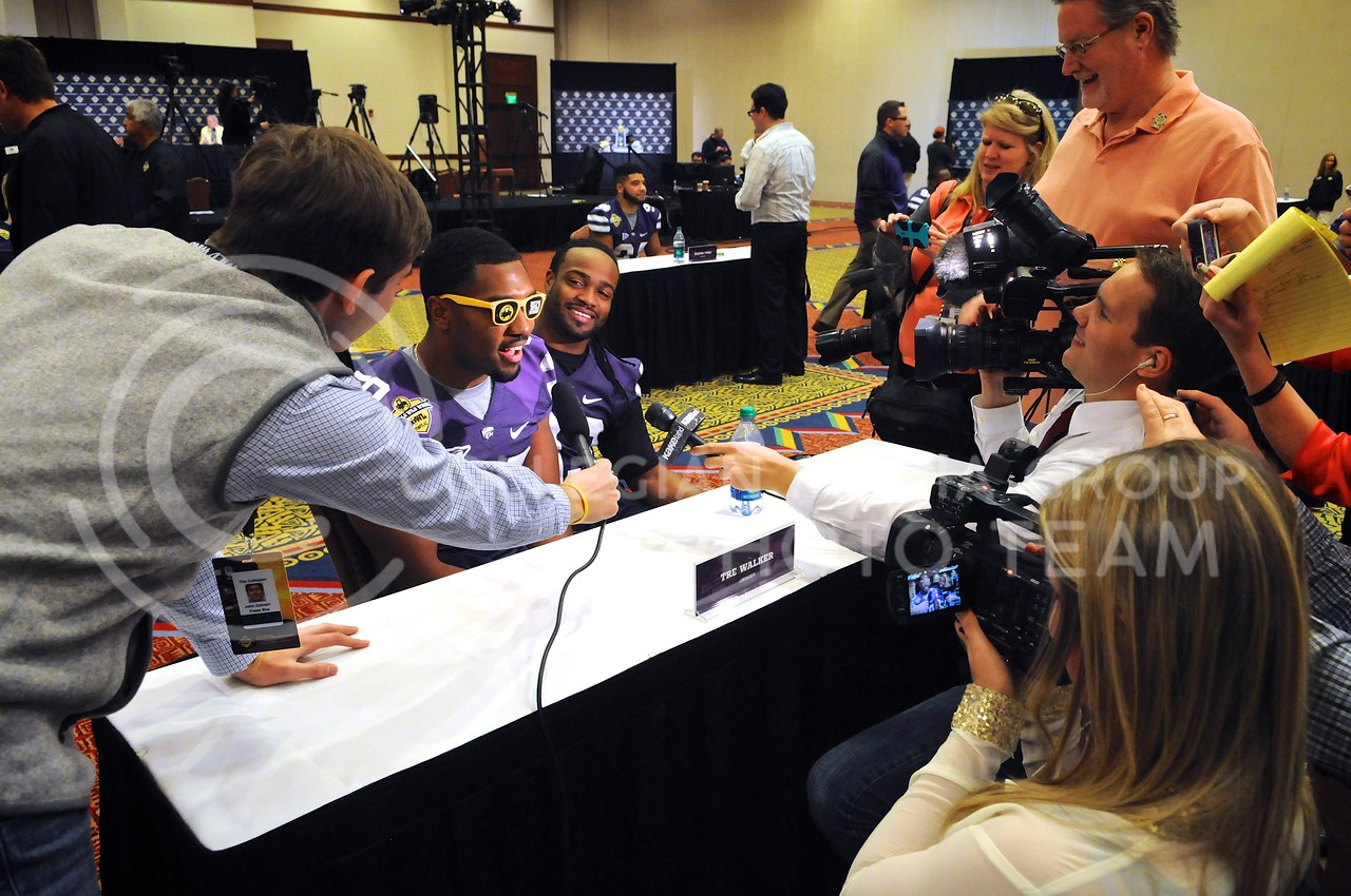 "(Photo by Parker Robb | Collegian)<br /> <br /> Members of the media flock around senior linebacker Tre Walker and senior running back John Hubert after they sang their own rendition of ""My Girl"" in response to a question on secret talents among the wildcat roster during K-State's Buffalo Wild Wings Bowl media day December 26, 2013."