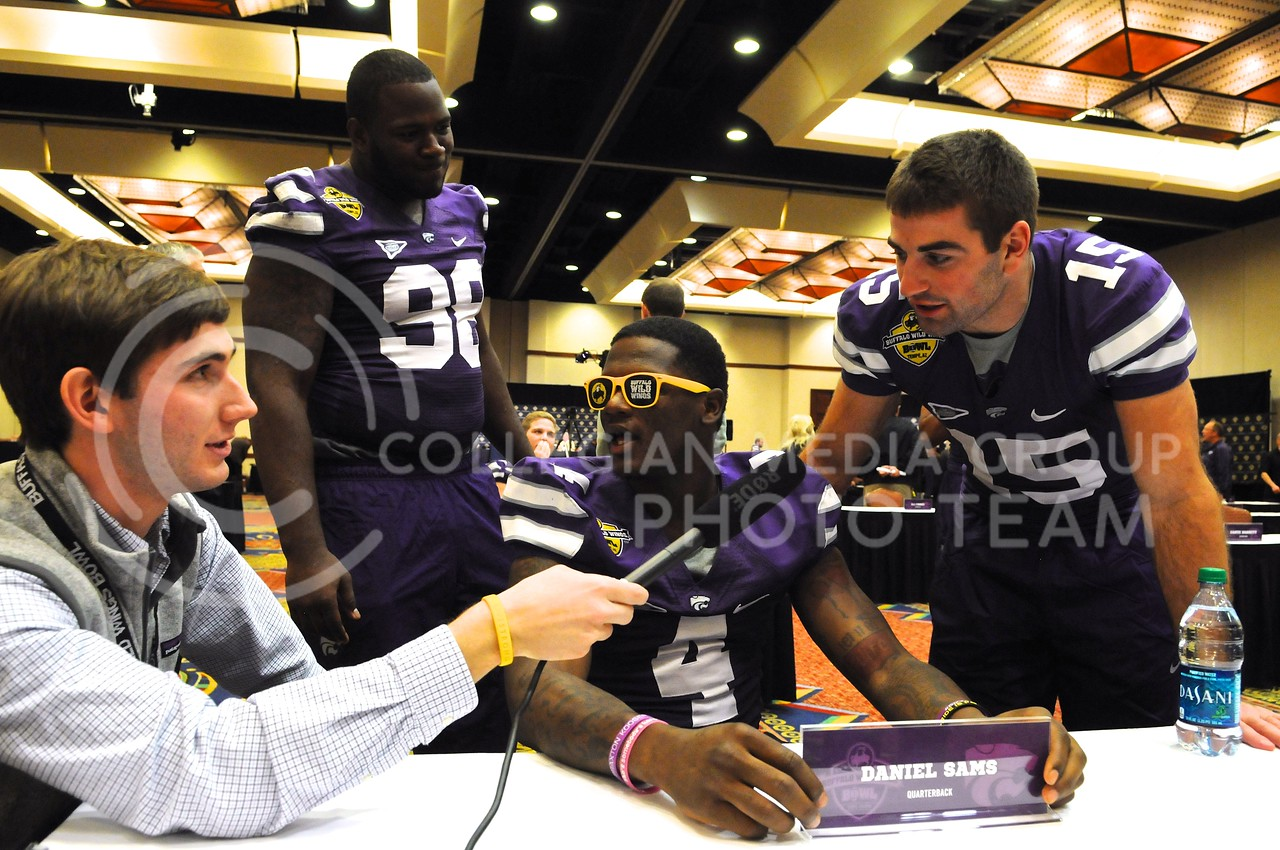 (Photo by Parker Robb | Collegian)<br /> <br /> From right to left, junior quarterback Jake Waters, sophomore quarterback Daniel Sams and senior defensive lineman Chaquil Reed respond to questions from the media about who among them would win a wing eating contest during K-State's Buffalo Wild Wings Bowl media day December 26, 2013.