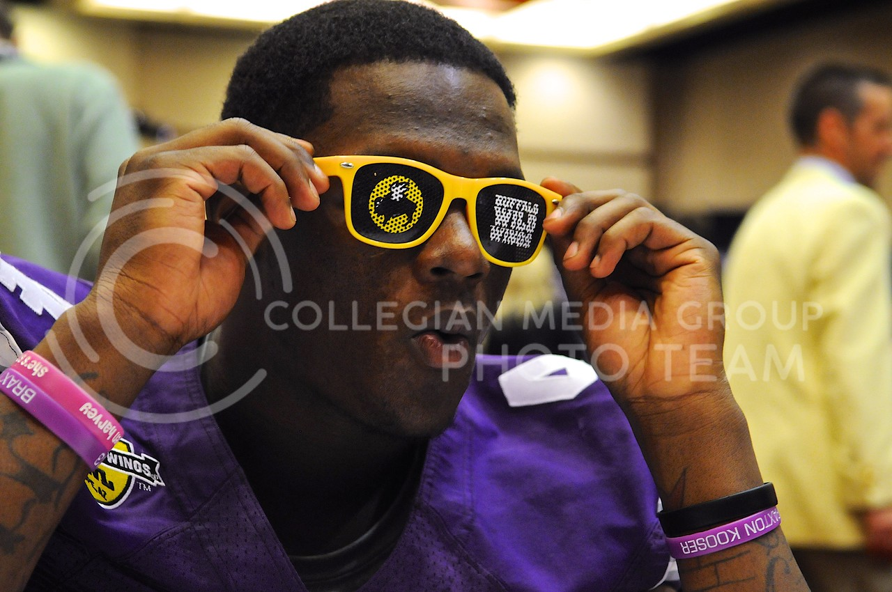 (Photo by Parker Robb | Collegian)<br /> <br /> Sophomore quarterback Daniel Sams ogles with glee as he puts on a pair of Buffalo Wild Wings shades during K-State's Buffalo Wild Wings Bowl media day December 26, 2013.