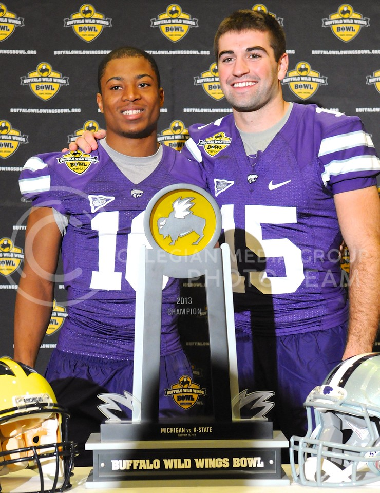 (Photo by Parker Robb | Collegian)<br /> <br /> Junior wide receiver Tyler Lockett and junior quarterback Jake Waters embrace behind the Buffalo Wild Wings Bowl champion's trophy during K-State's Buffalo Wild Wings Bowl media day December 26, 2013.