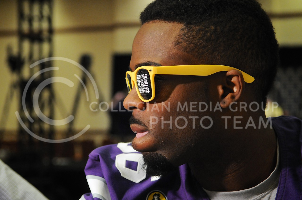 (Photo by Parker Robb | Collegian)<br /> <br /> Senior wide receiver Tramaine Thompson models a pair of Buffalo Wild Wings sunglasses during K-State's Buffalo Wild Wings Bowl media day December 26, 2013.