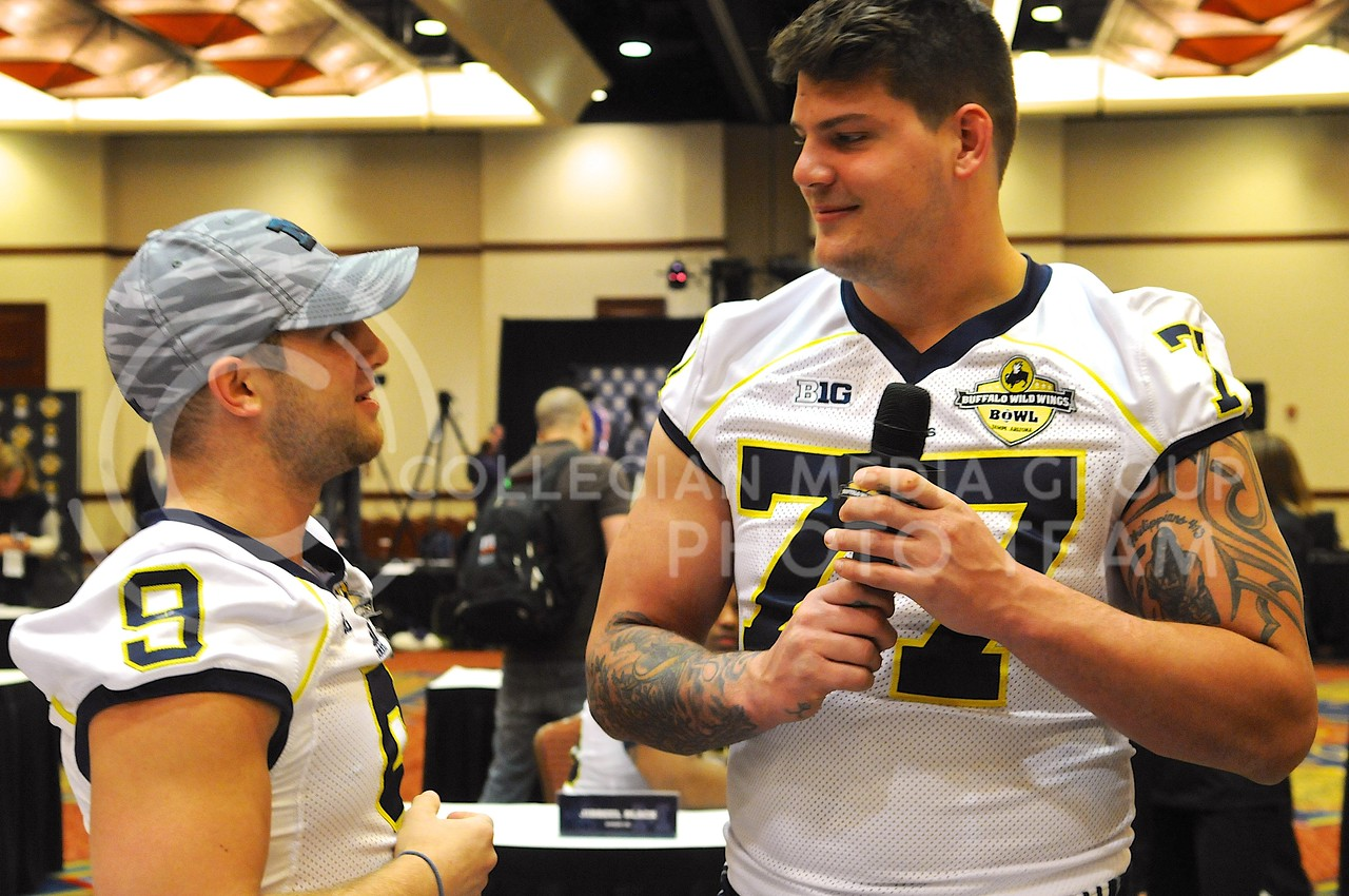(Photo by Parker Robb | Collegian)<br /> <br /> Michigan offensive lineman Taylor Lewan steal the microphone away from wide receiver Drew Dileo when he became dissatisfied with Dileo's interviewing style during Michigan's Buffalo Wild Wings Bowl media day December 26, 2013.