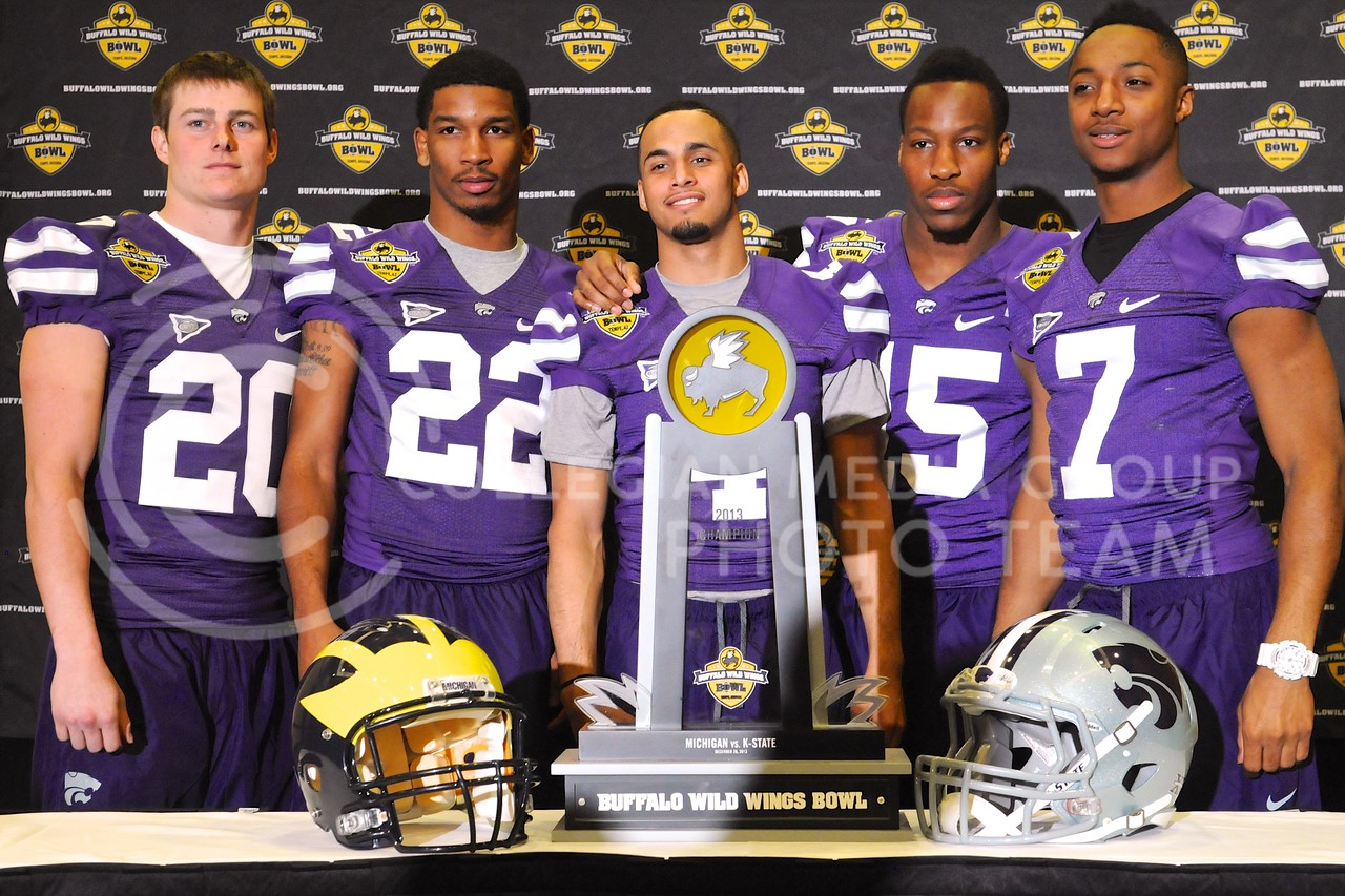 (Photo by Parker Robb | Collegian)<br /> <br /> Defensive backs Dylan Schellenberg, Dante Barnett, Dorrian Roberts, Randall Evans and Kip Daily pose behind the Buffalo Wild Wings Bowl champion's trophy during K-State's Buffalo Wild Wings Bowl media day December 26, 2013.